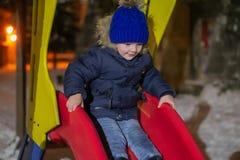 Un muchacho de tres años en ropa diaria del invierno está bajando una colina Él es feliz y goza el jugar en el frío foto de archivo libre de regalías