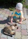 Un muchacho del año que juega con el gato Fotografía de archivo libre de regalías