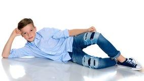 Un muchacho del adolescente miente en un fondo blanco Foto de archivo libre de regalías
