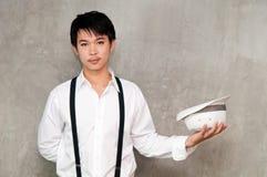 Un muchacho del adolescente sostiene el sombrero en su mano Foto de archivo libre de regalías