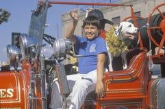 Un muchacho del Latino en un coche de bomberos Foto de archivo