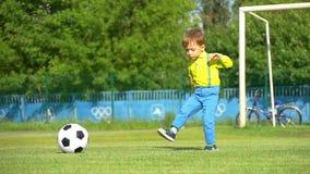 Un muchacho del niño en el estadio golpea un balón de fútbol con el pie en una cámara lenta almacen de metraje de vídeo