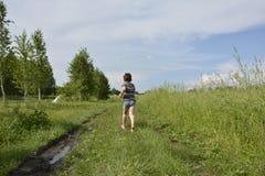 Un muchacho del pueblo corre abajo del camino en el campo Fotografía de archivo libre de regalías