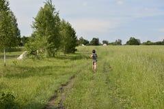 Un muchacho del pueblo corre abajo del camino en el campo Imagen de archivo