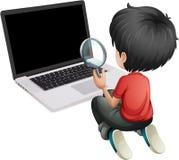 Un muchacho delante de un ordenador portátil que sostiene una lente que magnifica Imagenes de archivo