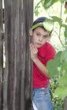 Un muchacho detrás de la cerca Foto de archivo libre de regalías