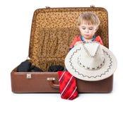 Un muchacho divertido con el sombrero está en la maleta imagenes de archivo