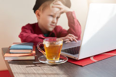 Un muchacho emocional del llitle que lleva la ropa de moda y el casquillo sittiing en la tabla que trabaja con su ordenador portá Imágenes de archivo libres de regalías