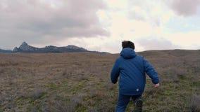 Un muchacho en campo con las flores amarillas corre al horizonte con las rocas vídeo de la cámara lenta almacen de video