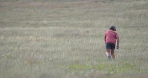 Un muchacho en casquillo está caminando a lo largo del fuerte viento de la cuesta de la colina está soplando metrajes