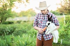 Un muchacho en conejo de alimentación del desgaste del vaquero con la zanahoria en granja Fotos de archivo libres de regalías