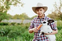 Un muchacho en conejo de alimentación del desgaste del vaquero con la zanahoria en granja Imagen de archivo libre de regalías