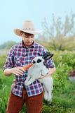 Un muchacho en conejo de alimentación del desgaste del vaquero con la zanahoria en granja Fotografía de archivo libre de regalías