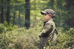 Un muchacho en el bosque, colocándose entre árboles, coloca el sidewaysd fotos de archivo