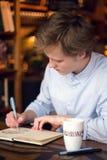 Un muchacho en el dibujo de la camisa en el cuaderno Fotografía de archivo