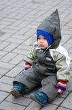 Un muchacho en el snowsuit verde que se sienta en piedra de pavimentación Imagen de archivo libre de regalías