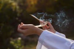 Un muchacho en un kimono sostiene un palillo ardiente del incienso, realizando un mi Fotos de archivo libres de regalías