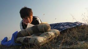 Un muchacho en la naturaleza que lee un libro en los rayos de la puesta del sol almacen de metraje de vídeo