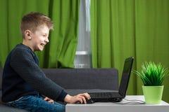 Un muchacho en un ordenador port?til juega a juegos, o mira un v?deo El concepto de apego a los juegos de ordenador, visi?n borro imagen de archivo libre de regalías