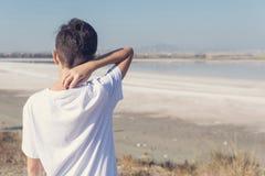 Un muchacho en pantalones cortos y una camiseta cerca del lago de sal en Larnaca fotografía de archivo