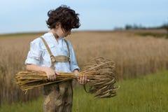 Un muchacho en ropa bávara tradicional se coloca en el campo Imagenes de archivo