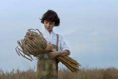 Un muchacho en ropa bávara tradicional se coloca en el campo Fotos de archivo libres de regalías
