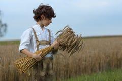 Un muchacho en ropa bávara tradicional se coloca en el campo Fotografía de archivo libre de regalías