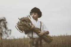Un muchacho en ropa bávara tradicional se coloca en el campo Imagen de archivo libre de regalías