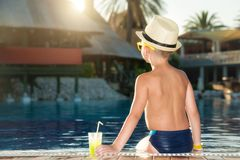 Un muchacho en un sombrero de paja con un cóctel a disposición que se sienta en la piscina fotografía de archivo