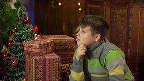 Un muchacho en un suéter cerca del árbol de navidad en casa, considerando los regalos, esperando en el fondo de las luces de la N almacen de metraje de vídeo