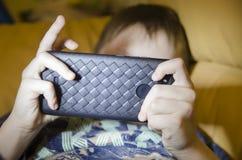 Un muchacho en su teléfono foto de archivo
