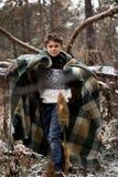 Un muchacho en tela escocesa camina en la nieve en el bosque solamente i del otoño Imagen de archivo