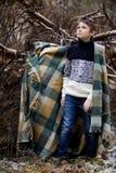 Un muchacho en tela escocesa camina en la nieve en el bosque solamente i del otoño Imagenes de archivo