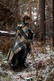 Un muchacho en tela escocesa camina en la nieve en el bosque solamente i del otoño Imágenes de archivo libres de regalías