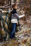 Un muchacho en tela escocesa camina en la nieve en el bosque solamente i del otoño Fotografía de archivo