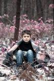 Un muchacho en tela escocesa camina en la nieve en el bosque solamente i del otoño Foto de archivo