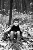 Un muchacho en tela escocesa camina en la nieve en el bosque solamente i del otoño Fotos de archivo