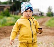 Un muchacho en un traje amarillo que sostiene una piedra disponible imagen de archivo