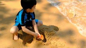 Un muchacho en traje de natación se está sentando en la playa y está jugando la arena almacen de metraje de vídeo