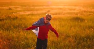 Un muchacho en un traje y una máscara del super héroe que corren a través del campo en la puesta del sol en la hierba almacen de video