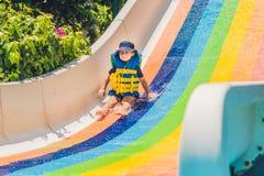 Un muchacho en un chaleco salvavidas resbala abajo de una diapositiva en un parque del agua Foto de archivo