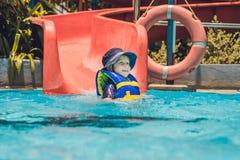 Un muchacho en un chaleco salvavidas resbala abajo de una diapositiva en un parque del agua Fotografía de archivo libre de regalías
