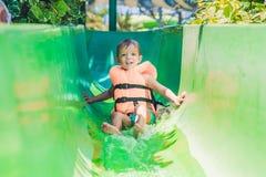 Un muchacho en un chaleco salvavidas resbala abajo de una diapositiva en un parque del agua Fotos de archivo libres de regalías