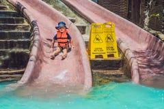 Un muchacho en un chaleco salvavidas resbala abajo de una diapositiva en un parque del agua Imagenes de archivo