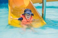 Un muchacho en un chaleco salvavidas resbala abajo de una diapositiva en un parque del agua Imagen de archivo