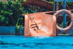 Un muchacho en un chaleco salvavidas resbala abajo de una diapositiva en un parque del agua Foto de archivo libre de regalías