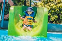 Un muchacho en un chaleco salvavidas resbala abajo de una diapositiva en un parque del agua Fotografía de archivo