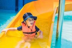 Un muchacho en un chaleco salvavidas resbala abajo de una diapositiva en un parque del agua Fotos de archivo