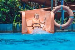 Un muchacho en un chaleco salvavidas resbala abajo de una diapositiva en un parque del agua Imágenes de archivo libres de regalías