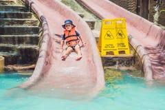 Un muchacho en un chaleco salvavidas resbala abajo de una diapositiva en un parque del agua Imagen de archivo libre de regalías